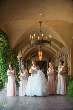 Bridesmaids wearing long pink sheath v-neck dresses designed by Bill Levkoff. Bouquets are smaller versions of the brides round bouquet with white, peach and pink roses, hydraenas, and stocks   Lasting Images Photography   villasiena.cc