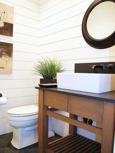 In a classic color combination of white, dark brown and black, this transitional powder room designed by Judith Balis is stylish and practical. White wood paneled walls add dimension while the round mirror provides a visual focal point.  A lone green plant adds just enough color and spare furnishings keep the look crisp and clean.
