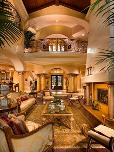 Mediterranean Style Living Room, with big columnsl large fireplace, European style furniture, antique accessories. Nice wrought iron railing on second floor overlooking living room. Large front door with large window above.