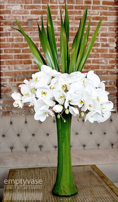 Empty Vase Florist / Treasured Love  Description: 60 Blooms of White Phalaenopsis Orchids decorated with Flax Leaves are arranged in...