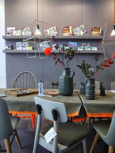 inspiration for our art studio - grey drop cloth covered tables with bits of orange and soft grey chairs