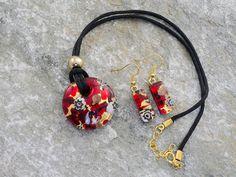 Parure un vetro di Murano con pendente rotondo, leggermente bombato, ed orecchini rettangolari.   Il laccio è in cotone nero.   Un pendente rosso con murrine sgargianti appoggiate su una foglia d'oro. Sembra un fiume di lava.