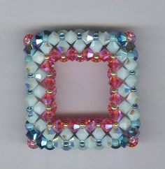 Swarovski Square Pendant made to hang on any chain. Elegant with radiant bright colors. Swarovski Blue Opal AB2X bicones with Indian Pink bicones and Jet AB2X crystals This original design will be wearable with any attire and certainly be admired by many. One of a kind exquisite design. Length is one inch and 1/4 around..