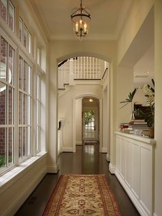 Hallway leading to foyer. Corridor features glass lantern over red and gold Persian rug layered over hardwood floors. Living room pass through faces bank of windows. So pretty Dream Home Design, My Dream Home, Home Interior Design, Appartement New York, Future House, My House, Dream Apartment, Aesthetic Rooms, House Goals