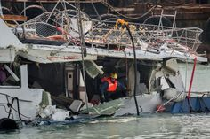 A fireman inspects the back end of the badly damaged Lamma IV passenger boat after a collision, near the shores of Hong Kong's Lamma island the morning after it was pulled out of the waters following its sinking on October 1. The captains of a ferry and the Lamma IV pleasure boat that collided in Hong Kong on October 1, killing 38 people in the city's worst maritime disaster in decades, were arrested on October 2 with five other crew, officials said. (Philippe Lopez/GettyImages)