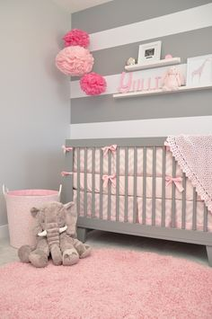 quarto de bebê decorado, parede de listras cinza e branco, tapete rosa, quarto de bebê menina, bebê feminino, berço cinza com laços cor de rosa, pompons cor de rosa na decoração