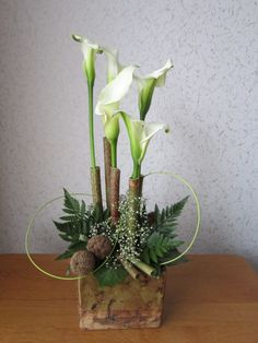 ~~ Calla classics~~ lovin the flowers in angle cut varigated bamboo, and that container looks handdone and rustic.