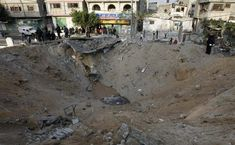 Palestinians inspect a crater caused by an Israeli air strike at a police station in Gaza City on December 29, 2008