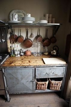Rustic metal cupboards, distressed wood countertops, and copper pots