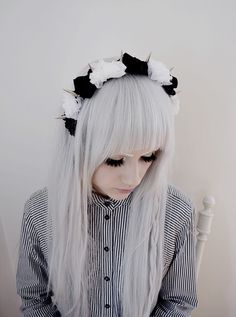 Silver hair, dramatic eyelashes and a crown of roses