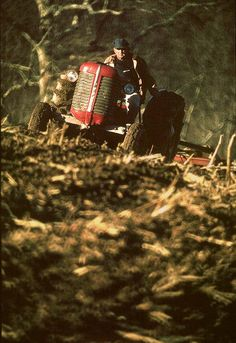 Spring Till     Farmer on old red tractor plowing corn field for spring planting