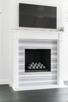 A large flat panel is mounted on a white wall above a white fireplace mantle accenting a fireplace surround covered in Delano Marble complimenting a black herringbone firebox.