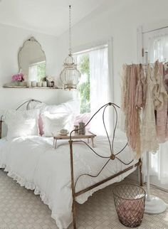 Crisp white bedding, a mirror, nice light fixture, subtle pink (flowers, scarves) and a lot of natural light. The wrought iron antique bed frame is the anchor of the room, with its dark color and material. Would love this for a little girls room.