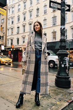 One of the most popular outwear picks this season is the long checked coat and we're taking notes on how to wear one with this extremely cool outfit inspiration from Gala Gonzalez. Beyond the coat, all you'll need are three key pieces: a grey ribbed knit sweater, cropped jeans, and black platform ankle boots. | ANDWHATELSEISTHERE