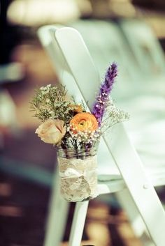 Mason jars filled with dainty flowers lined the aisle Photo byAnjuli - Project Wedding