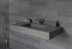 vasque design en granit fixée au mur revêtu de tuiles aspect granit
