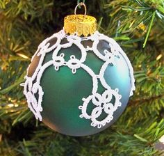 Display this elegant lace-covered ornament prominently on your tree or by itself on an ornament stand. The lace covering the colored glass ornament is needle-tatted with cotton crochet thread.    Your ornament comes wrapped securely in a gift box and shipped in a second box for safekeeping.