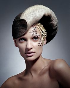 Just roll with it. A long brown straight top knot quirky avant garde hairstyle by D Ambrose