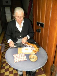 Woman making bobbin lace, Bruges Belgium. She is sitting in the doorway of her house.