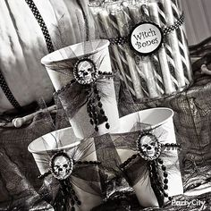 Add shocking style to white cups by stringing a rhinestone Halloween skull ring onto a short string of beads. Add some black feathers from a boa and some black tulle for a chilling gothic effect. Your ghoulfriends will love filling these up with candy sticks and gumballs for the broom ride home!
