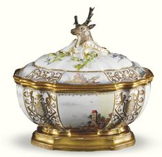 A Meissen tureen and cover circa 1740-1750 of Baroque form with stag's head finial, each piece with panels of figures in landscapes within elaborate black-edged gilt scrollwork (restored) Quantity: 2    Sotheby's
