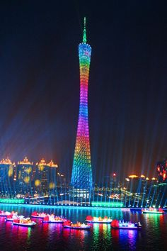 Canton tower is illuminated with multicoloured lights as colorful boats float on the water during the final rehearsal for the opening ceremony of the 16th Asian Games in Guangzhou