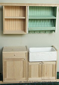 After assembling a range of cabinets for a dollhouse miniature kitchen, the cabinets should be test fitted before the base cabinets are set on a plinth and the upper cabinets are trimmed with crown moldings.