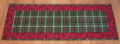 """This handmade Christmas table runner was made with cotton fabrics featuring Christmas plaid outlined in a Christmas holly design. Size is 12-1/2"""" x 34"""" (31-40-21)"""