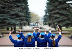 Backs of ecstatic students in graduation gowns holding diplomas by Pressmaster, via Shutterstock