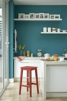 cuisine bleu canard, étagères en blanc poli, huit photos familiales aux cadres blancs, tabouret en bois corail, carrelage en beige