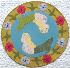 """Sea of the Mermaid Candle Mat Pattern. Finished Size 14 3/4"""" Circle Candle Mat   Betsy Lou Pattern Company was initiated by Betsy Moyer and Louann Edmiston in Findlay, Ohio. Both women were taught to sew at an early age by their mother and grandmother respectively and have been sewing ever since. The launch of their pattern company grew from their desire to share their sewing experiences with others."""