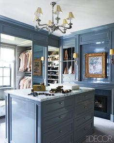 Dressing room customized for the number of handbags, heights of boots, and hanging measurements of the owner's clothing; interior design by Celerie Kemble #master #closet #dressing_room #chandelier #painting
