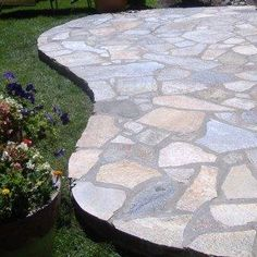 A raised flagstone patio spills out over a lush green lawn.