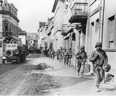 47th Inf Reg't of the 9th Inf Div marching thru Remagen to cross the Ludendorf bridge, Mar 1945