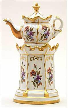 Teapot #500  Round base, hexagonal stand and pot; scalloped at top of both; white background, gold trim   with purple and yellow pansies in panels.  Acquired in Sevres, Paris