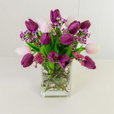 This contemporary and elegant artificial arrangement consists of many real touch purple tulips and other garden flowers. All are nicely arranged in the square g