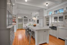 Sweet white kitchen; unique ceiling; great floors; great cabinets; transom windows above sink; black farm house sink; marble counters; stools and built-in book case
