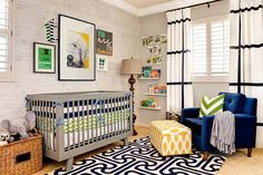 Gorgeous nursery with plantation shuttered windows dressed in black and white grid patterned drapes over pale gray walls. A distressed gray wood plank style wallpaper highlights the modern gray crib with navy blue and white striped crib bumper over green and white chevron bedding. A fun gallery wall with doggy art, framed bow ties and striped wall letter hangs over the crib with the words Read to Me over book ledges flanking the window. A yellow and white ikat dot ottoman pulls up to the Mid-Century style blue velvet tufted chair topped with a green and white chevron pillow and blue and white fringed throw. The beige wall to wall carpet is layered with a black and white geometric area rug which unites the space.