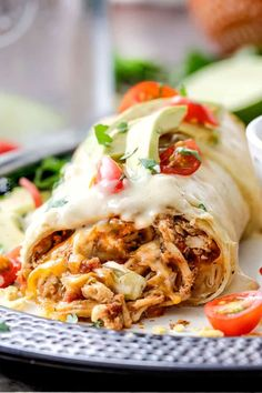 """Baked Chicken Burritos AKA """"skinny chimichangas"""" are restaurant delicious without all the calories! They are made super easy by stuffing them with the BEST slow cooker Mexican chicken, baking to golden perfection and smothering in most incredible Cheesy Green Chili Sour Cream Sauce."""