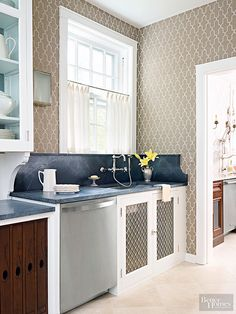 Kitchen wallpaper with a sophisticated Moroccan pattern adds visual interest to this monochromatic butler's pantry. The fresh stencil helps modernize a soapstone countertop and backsplash with authentic period charm. Neutral Kitchen Wallpaper, Kitchen Wallpaper Design, Kitchen Design, Kitchen Ideas, Brown Kitchen Tiles, Kitchen Colors, Kitchen Desk Areas, Lush, Parisian Kitchen