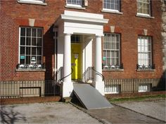 This ramp at the entrance to an historic building is exceptionally steep. It would be very difficult to push a wheechair up the ramp because of its gradient and impossible to self propel a manual wheelchair. The surface of the ramp is very shiny and looks slippery which would add to the difficulty. There are no edges or rails to the ramp to prevent slipping off the edge.  Image courtesy of Sandra Manley. Manual Wheelchair, Entrance, Surface, Museum, Building, Image, Design, Appetizer, Construction