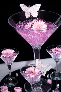 Gel Martini Glass Decoration @ £25.00 per table : A beautiful large Martini gladd filled with gel beads and surrounded by 3 mini Martini glasses each filled with gel beads and topped with co-ordinating flowers. The price includes the glass ware and contents plus large mirror plate, scatter crystals and petals