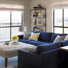 Blue Sectional with Light Gray Tufted Ottoman as Coffee Table