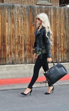 Acheter la tenue sur Lookastic:  https://lookastic.fr/mode-femme/tenues/veste-motard-t-shirt-a-col-rond-jean-skinny-escarpins-sac-fourre-tout-lunettes-de-soleil-collier/6375  — T-shirt à col rond camouflage vert foncé  — Lunettes de soleil brunes  — Collier doré  — Veste motard en cuir noire  — Sac fourre-tout en cuir noir  — Jean skinny noir  — Escarpins en daim noirs