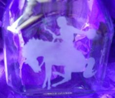 This is an home made etching on a jar of a cowboy and horse.