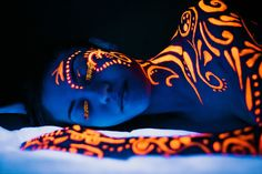 UV Black Light Orange Body Paint On Girl On Her Side