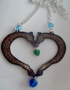 http://www.artfire.com/ext/shop/product_view/MuddSlingerCeramicsandCrafts/4298259/Giraffes_in_Love_OOAK/Jewelry/Necklaces/Plastic