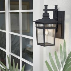 Effortlessly enhance your outdoor space with this one-light outdoor wall lantern. Made from aluminum in a charming weather-resistant finish, this island colonial-style design features a long rectangular backplate, angular arm with decorative finials, pagoda-inspired molding, and seeded glass panels around a simple square frame. For a tropical seating arrangement for you and your better half to enjoy a starless night in, place a glass-top side table between two wicker arm chairs with piped…