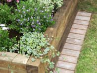 Railroad ties are good to use for a raised bed planter. If the raised bed is adjacent to a lawn, make maintenance easier by laying down a mowing strip of bricks to make trimming easier