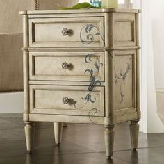 """Three-drawer accent chest with a floral motif and wallpapered interiors.     Product: Accent chest        Construction Material: Hardwood solids    Color: Antique white Features:Three drawers with a wallpapered interiorFloral motif    Dimensions: 28"""" H x 21"""" W x 14"""" D"""